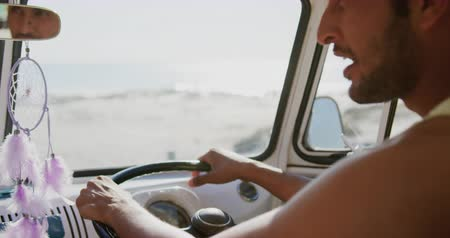 roupa de praia : Over the shoulder view of a young Asian man sitting in the driving seat of a camper van parked at a beach, looking out of the window and pointing, turning and talking. Summer Road Trip in Camper Van to the beach with friends 4k Vídeos