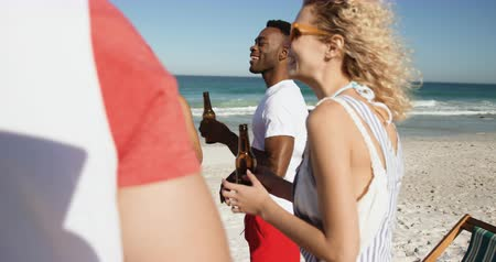 пляжная одежда : Close up of a multi-ethnic group of happy young adult male and female friends hanging out on a beach together, standing and drinking beers 4k