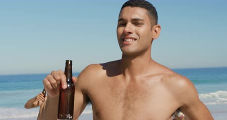 пляжная одежда : Close up of a young Asian man holding a bottle of beer and dancing on a beach with his friends 4k Стоковые видеозаписи