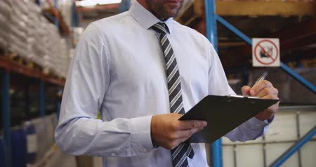 red tie : Close up of middle aged Caucasian male warehouse manager holding a clipboard and writing in a warehouse. They are working in a freight transportation and distribution warehouse. Industrial and industrial workers concept 4k