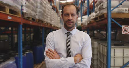 red tie : Close up portrait of middle aged Caucasian male warehouse manager with arms crossed standing in a warehouse, smiling to camera and laughing, while a wharehouse worker walks past. They are working in a freight transportation and distribution warehouse. Ind Stock Footage