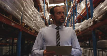 red tie : Close up front view of middle aged Caucasian male warehouse manager holding a clipboard and checking stock in a warehouse. Warehouse staff walk past him as he works. They are working in a freight transportation and distribution warehouse. Industrial and i Stock Footage