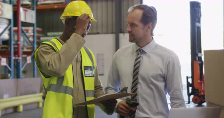 kod kreskowy : Close up of a middle aged Caucasian male warehouse manager holding a barcode scanner and a young African American male warehouse worker writing on a clipboard. The two men are standing by a stack of boxes in a warehouse loading bay looking at a laptop com
