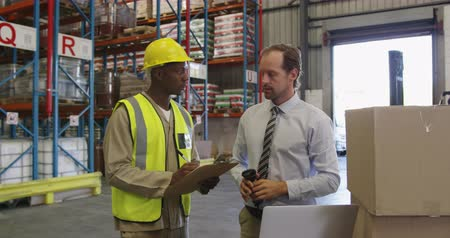 kod kreskowy : Front view of a middle aged Caucasian male warehouse manager holding a barcode scanner and a young African American male warehouse worker holding a clipboard standing by a stack of boxes in a warehouse loading bay talking, looking at a laptop computer, po