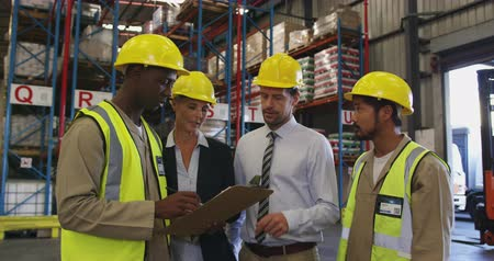 panoya : Front view close up of middle aged Caucasian female and male warehouse managers, a young African American and a young Asian male manual worker having a meeting in the loading bay of a warehouse, talking and looking at a clipboard. They are all wearing yel Stok Video