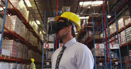 на камеру : Close up front view of middle aged Caucasian male warehouse manager waering VR headset and yellow hard hat, standing in the loading bay of a warehouse and looking around.  In the background warehouse staff walk around the storage shelves. They are working