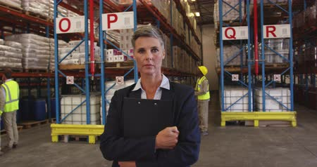engradado : Portrait close up of a middle aged Caucasian female warehouse manager looking straight to camera, holding clipboard to her chest. In the background warehouse staff walk around the storage shelves. They are working in a freight transportation and distribut