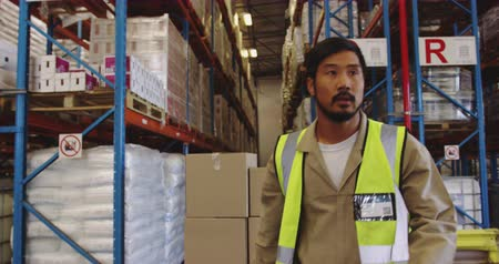 engradado : Close up of a young Asian male warehouse worker moving boxes on a trolley from storage shelves to the loading bay of a warehouse. They are working in a freight transportation and distribution warehouse. Industrial and industrial workers concept 4k