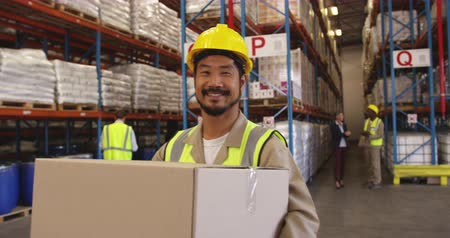 hard hat : Close up portrait of a young Asian male warehouse worker wearing a yellow hard hat and carrying a box, smiling to camera. In the background warehouse staff walk around the storage shelves. They are working in a freight transportation and distribution ware