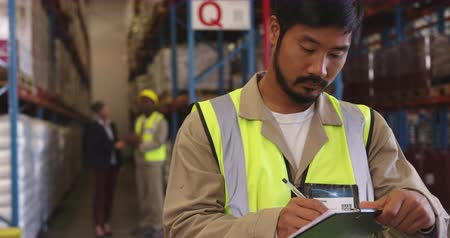организации : Front view close up of a young Asian male warehouse worker writing on a clipboard in a warehouse and walking out of shot. In the background warehouse staff are standing near the storage shelves talking. They are working in a freight transportation and dis