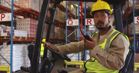 vorkheftruck : Close up of a young Asian male warehouse worker wearing a yellow hard hat sitting in a forklift truck using a two-way radio in a warehouse loading bay. In the background warehouse staff walk around the storage shelves. They are working in a freight transp
