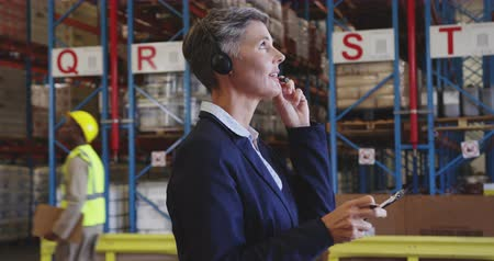 engradado : Close up side view of a middle aged Caucasian female warehouse managerusing a two-way radio headset and writing on a clipboard in a warehouse loading bay. In the background warehouse staff walk past the storage shelves. They are working in a freight trans