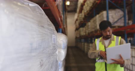 trabalhar : Close up of a young Asian male warehouse worker using barcode scanner and laptop computer to log goods stored in the warehouse. They are working in a freight transportation and distribution warehouse. Industrial and industrial workers concept 4k