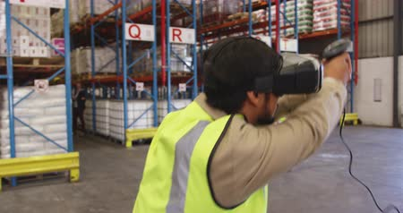kod kreskowy : Close up front view of a young Asian male warehouse worker jumping around playing with a VR headset and barcode scanner in a warehouse loading bay. In the background a male worker walks past watching him in disbelief. They are working in a freight transpo
