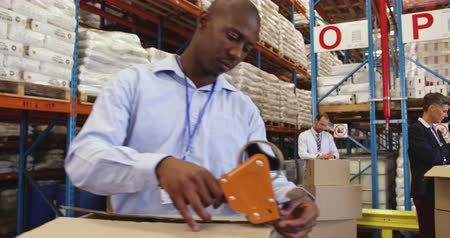 crate : Close up front view of a young African American man packing a box for delivery in a warehouse loading bay. In the background colleagues are also prepapring boxes for delivery. They are working in a freight transportation and distribution warehouse. Indust Stock Footage
