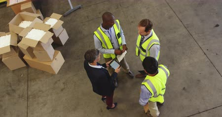 organizacja : Elevated view of middle aged Caucasian female warehouse manager briefing a multi-ethnic group of male staff, who shake hands before they all walk away. She is holding a tablet computer, the men are all carrying clipboards. They are working in a freight tr