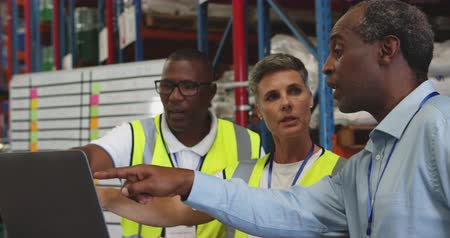 engradado : Close up of a middle aged Caucasian woman, a middle aged African American man and a young African American man working together, in discussion around a laptop in the loading bay of a warehouse. They are working in a freight transportation and distribution