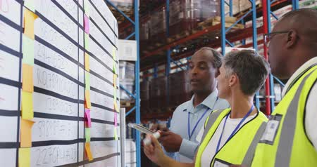 organisation : Close up of a middle aged Caucasian woman, a middle aged African American man and a young African American man working together, in discussion at an infromation board in the loading bay of a warehouse. They are working in a freight transportation and dist