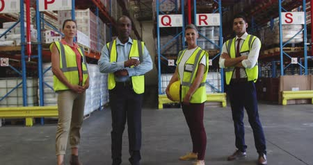 engradado : Portrait of a diverse group of warehouse workers, who walk towards camera, and stand together in a warehouse loading bay, looking to camera smiling. They are working in a freight transportation and distribution warehouse. Industrial and industrial workers