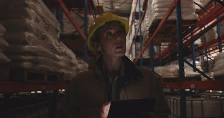 patrol : Close up front view of a young Caucasian female warehouse worker wearing a yellow hard hat and using a tablet computer while she patrols the corridors of a warehouse at night. They are working in a freight transportation and distribution warehouse. Indust Stock Footage