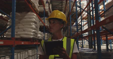 hard hat : Close up front view of a middle aged Caucasian female warehouse worker wearing a yellow hard hat and using a tablet computer while she patrols the corridors of a warehouse at night. They are working in a freight transportation and distribution warehouse.  Stock Footage