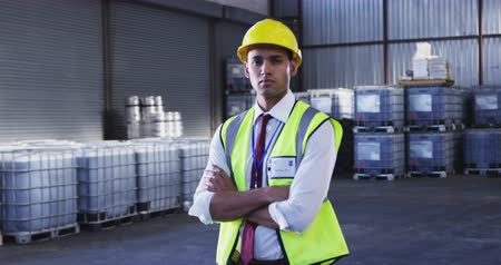 w : Portrait close up of a young Asian male warehouse worker wearing a yellow hard hat, standing in a storeroom with arms crossed, looking straight to camera. They are working in a freight transportation and distribution warehouse. Industrial and industrial w
