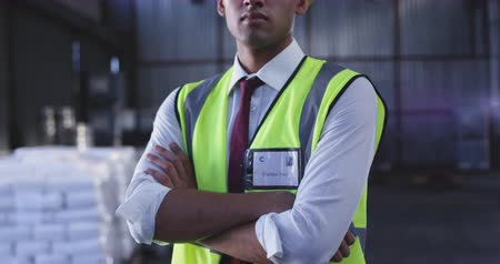 w : Portrait close up of a young Asian male warehouse worker wearing a yellow hard hat, standing in a storeroom, crossing arms and looking straight to camera. They are working in a freight transportation and distribution warehouse. Industrial and industrial w