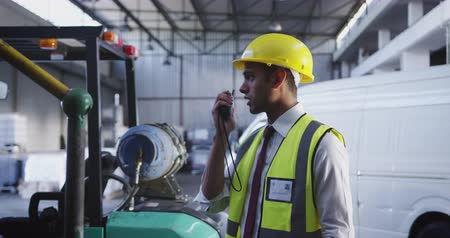 hard hat : Close up side view of a young Asian male warehouse worker standing in a warehouse loading bay talking on a two-way radio. They are working in a freight transportation and distribution warehouse. Industrial and industrial workers concept 4k