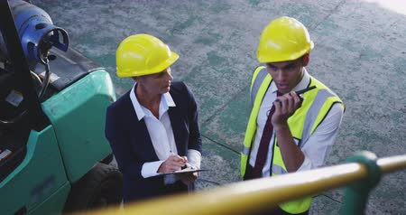 hard hat : Elevated close up view of middle aged Caucasian female warehouse manager and young Asian male warehouse manager wearing yellow hard hats talking in a warehouse, he is also talking on a two-way radio. They are working in a freight transportation and distri