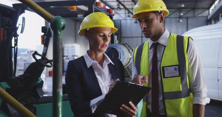 hard hat : Close up front view of a middle aged Caucasian female warehouse manager and a young Asian male warehouse manager talking in a warehouse loading bay. She is making notes on a clipboard. They are both wearing yellow hard hats. They are working in a freight