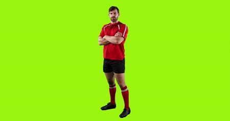 носок : Animation of a full length view of a young Caucasian male rugby player standing with arms crossed on a bright green background 4k