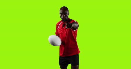 rugby shirt : Animation of a young African American male rugby player standing, looking to camera and playing with a rugby ball and pointing to camera on a bright green background 4k