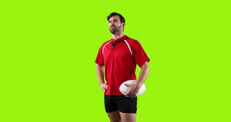 tenso : Animation of a young Caucasian male rugby player standing, looking around and holding a ball in his hand on a bright green background 4k