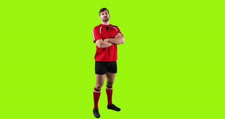 tenso : Animation of a full length view of a young Caucasian male rugby player standing with arms crossed on a bright green background 4k