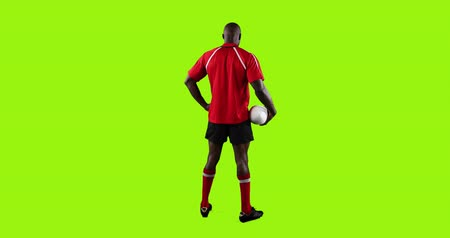 tenso : Animation of a full length rear view of a young African American male rugby player standing and holding a ball in his hand on a bright green background 4k