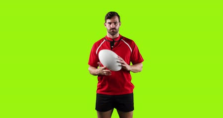 tenso : Animation of a young Caucasian male rugby player standing, looking to camera and playing with a ball on a bright green background 4k