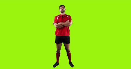 rugby shirt : Animation of a full length view of a young Caucasian male rugby player standing with arms crossed on a bright green background 4k