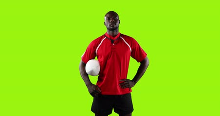 rugby shirt : Animation of a young African American male rugby player standing, looking to camera and holding a ball under his arm on a bright green background 4k Stock Footage