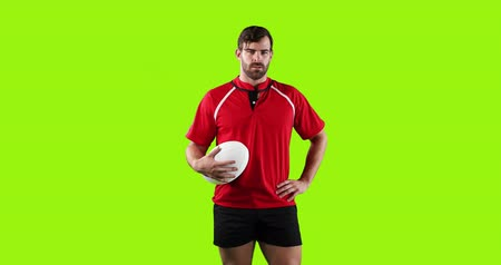 tenso : Animation of a young Caucasian male rugby player standing, looking to camera and holding a ball in his hand on a bright green background 4k Vídeos
