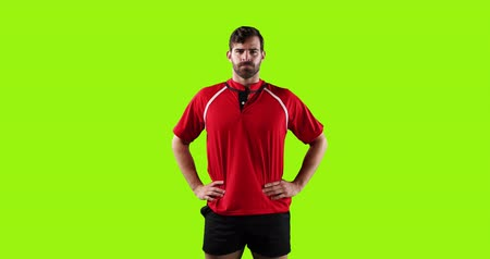 rúgbi : Animation of a young Caucasian male rugby player concentrating and standing with hands on hips on a bright green background 4k