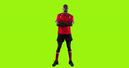 tenso : Animation of a full length view of a young African American male rugby player standing with arms crossed on a bright green background 4k Vídeos