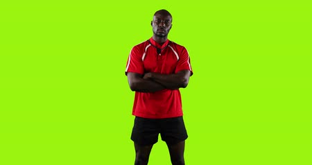 rugby shirt : Animation of a young African American male rugby player standing with arms crossed on a bright green background 4k