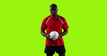 rugby shirt : Animation of a young African American male rugby player standing, looking to camera and playing with a ball on a bright green background 4k