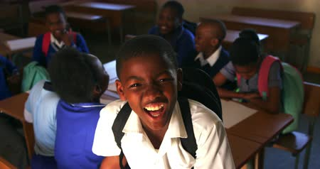 školák : Portrait close up of a young African schoolboy wearing his school uniform and schoolbag, looking up to camera smiling, at a township elementary school with classmates sitting at desks in the background 4k