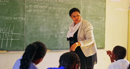 концентрированный : Rear view close up of a middle aged African female school teacher standing at the front of the class writing on the blackboard with pupils watching from their desks during a lesson in a township elementary school classroom 4k