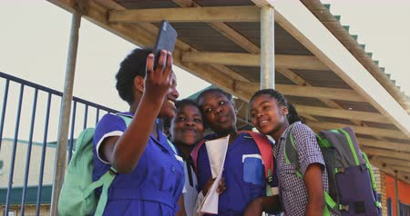 spolužák : Front view close up of a group of young African schoolgirls having fun posing and taking selfies with a smartphone in a township elementary school playground 4k