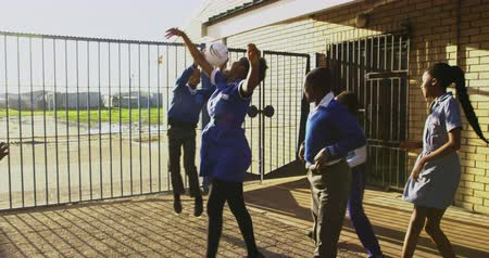 recess : Slow motion front view of a group of young African schoolgirls and schoolboys jumping and playing with a ball by a fence in the playground at a township elementary school 4k