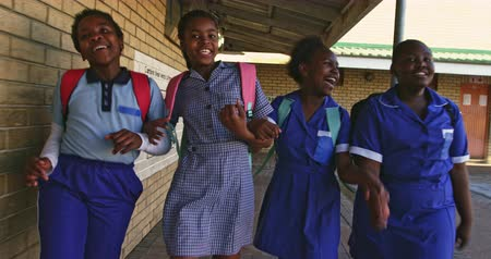 recess : Front view close up of four young African schoolgirls running in the school yard carrying schoolbags at a township elementary school 4k Stock Footage