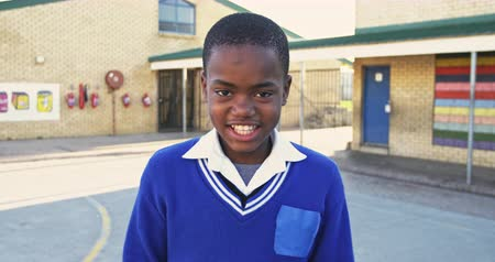 školák : Portrait close up of a young African schoolboy wearing his school uniform and schoolbag, looking to camera smiling in the playground at a township elementary school 4k