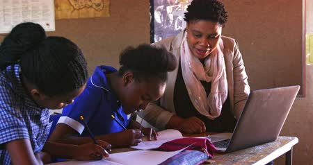 kaapstad : Front view close up of a middle aged African female school teacher helping a young African schoolgirl sitting at her desk using a laptop computer during a lesson in a township elementary school classroom, while beside her and in the background classmates